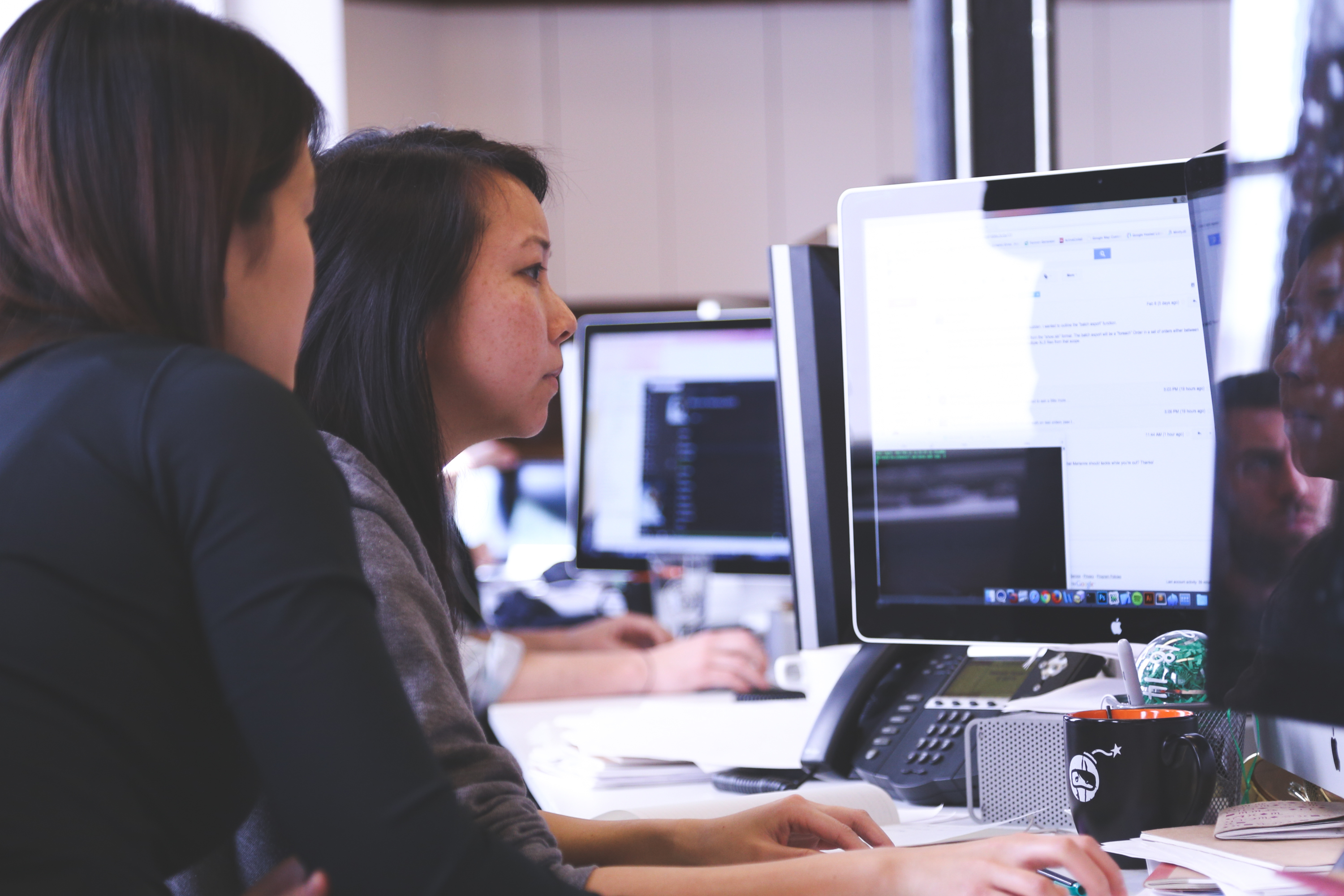 Two Women Sitting in Front of Computer Monitor